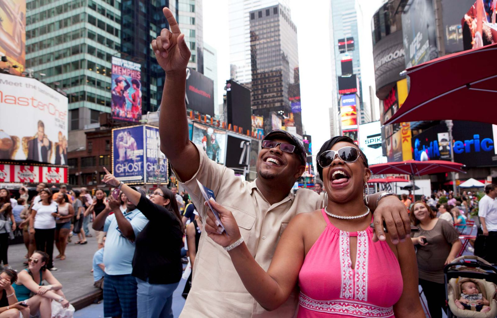 Participants in Times Square reacting to their video on the billboard